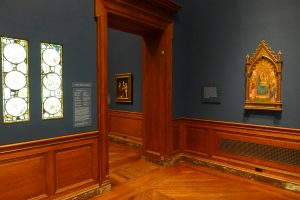 Installation view of first room of European Galleries at the Baltimore Museum of Art showing composite window of late medieval glass and tempera painting of Madonna and Child Enthroned by Circle of Niccolo di Pietro Gerini. Photograph by author, 2018.